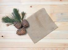 La branche de cèdre avec des cônes sur des tissus de vintage sur une texture en bois Photographie stock