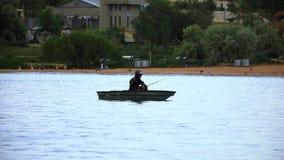 La branche de cassis dans le pêcheur de matin pêche des poissons dans le lac banque de vidéos