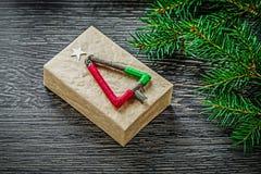 La branche de sapin a emballé la boîte actuelle sur le conseil en bois Photographie stock libre de droits