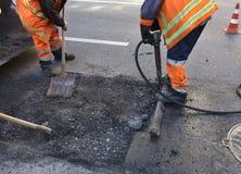 La brigata del ` dei lavoratori rimuove una parte dell'asfalto con le pale nella costruzione di strade fotografie stock libere da diritti