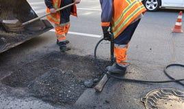 La brigata del ` dei lavoratori rimuove una parte dell'asfalto con le pale nella costruzione di strade immagini stock libere da diritti