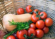 La brindille avec des tomates, l'oignon, le potiron et le romarin dans un osier se dorent Photographie stock libre de droits