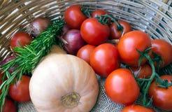 La brindille avec des tomates, l'oignon, le potiron et le romarin dans un osier se dorent Photographie stock