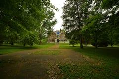 La brique de vintage et la maison classiques de pierre se sont nichées dans les arbres très hauts dans la cour photographie stock