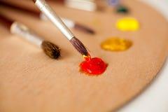 La brocha profesional sumergió en pintura de aceite roja en la paleta Fotografía de archivo libre de regalías