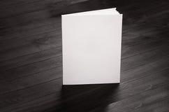 La brochure de blanc d'identité d'entreprise se tenant sur le fond en bois élégant noir, raillent  Photo stock