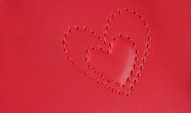 La broderie dans la forme de deux coeurs a niché dans l'un l'autre, sur la goupille Photo libre de droits