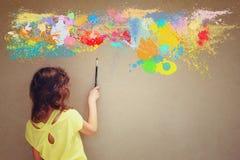La brosse mignonne de participation d'enfant de vue arrière à côté du mur et de la peinture texturisés éclabousse photographie stock