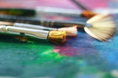 La brosse pelucheuse se trouve sur la palette peinte avec de l'huile multicolore images stock