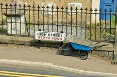 La brouette de roue est partie par des ouvriers à côté de la plaque de rue élevée au Pays de Galles tandis que sur une coupure photo stock