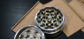 La broyeur argentée métallique pour des bourgeons de marijuana nlying sur la fumée empaquette le plan rapproché Légalisez le conc Images stock