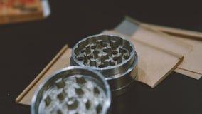 La broyeur argentée métallique pour des bourgeons de marijuana nlying sur la fumée empaquette le plan rapproché Légalisez le conc Image libre de droits