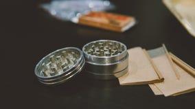 La broyeur argentée métallique pour des bourgeons de marijuana nlying sur la fumée empaquette le plan rapproché Légalisez le conc Images libres de droits