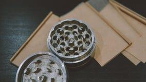 La broyeur argentée métallique pour des bourgeons de marijuana nlying sur la fumée empaquette le plan rapproché Légalisez le conc Photographie stock