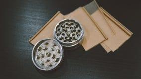 La broyeur argentée métallique pour des bourgeons de marijuana nlying sur la fumée empaquette le plan rapproché Légalisez le conc Photos stock