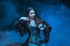 La bruja con la bola mágica en sus manos causa bebidas espirituosas imagenes de archivo