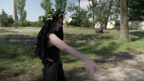 La bruja de la magia negra en un vestido gótico que caminaba y que llamaba con bebidas espirituosas de la mano de demonios recole almacen de video