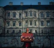 La bruja de la mujer sostiene la maleta con las flores en sus manos Imágenes de archivo libres de regalías