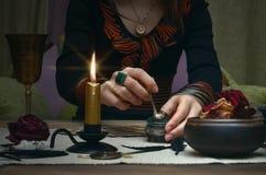 La bruja de la mujer prepara una poción mágica Tarjetas de Tarot Lectura futura Concepto del adivino fotos de archivo libres de regalías