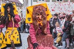 La bruja divertida lanza confeti rojo en el aire Carnaval de la calle en Alemania meridional - bosque negro fotografía de archivo
