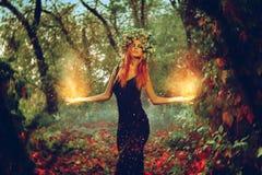 La bruja elegante de la muchacha del redhair conjura en el bosque mágico Fotografía de archivo libre de regalías