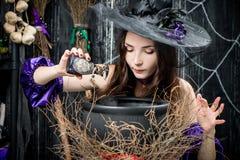 la bruja en un sombrero negro en un pote cocina imagenes de archivo