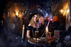 La bruja está conjurando por la luz de una vela Fotografía de archivo