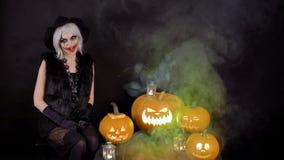 La bruja hermosa asustadiza de la muchacha celebra Halloween con las calabazas ardientes que brillan intensamente divertidas en h almacen de video