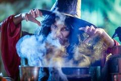 La bruja joven está cocinando con magia imágenes de archivo libres de regalías