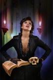 La bruja moderna del sexi echa un encanto en el viejo fondo Fotografía de archivo