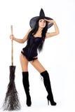 La bruja, sosteniendo una escoba, mira en Fotografía de archivo