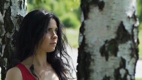 La brune attrayante recherche se tenante sous un arbre en parc, pensées d'avenir banque de vidéos