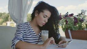 La brune avec du charme détendent à la terrasse d'été et introduisent le message au téléphone banque de vidéos