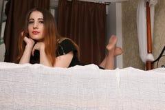 La brune avec du charme se trouve sur le grand lit et regarder vers le bas Image libre de droits