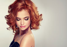 La brune avec la longueur moyenne a courbé des cheveux et lumineux composez photo stock