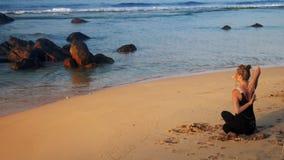 La brune calme médite sur la plage sablonneuse sous la lumière du soleil clips vidéos