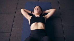 La brune d'Attarctive dans les vêtements de sport noirs faisant l'ABS de torsion de la cellule s'exerce pour réaliser les muscles banque de vidéos