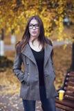 La brune de fille en parc en verres de port de manteau, automne ou printemps, marche dans la ville, attendant des amies Youn Photo libre de droits