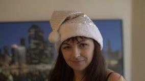 La brune de Noël se tourne et souriant vers l'appareil-photo dans le chapeau de Santa, portrait clips vidéos
