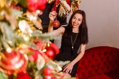 La brune de sourire décore un arbre de Noël femme de brune tenant une boule de Noël dans sa main photos libres de droits