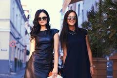 La brune deux sexy portant le noir élégant s'habille dans des lunettes de soleil, posant près d'un café de terrasse dans une vill Photos libres de droits