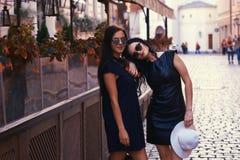 La brune deux sexy portant le noir élégant s'habille dans des lunettes de soleil, posant près d'un café de terrasse dans une vill Photographie stock