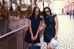 La brune deux sexy portant le noir élégant s'habille dans des lunettes de soleil, posant près d'un café de terrasse dans une vill Photo stock