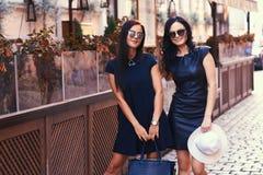 La brune deux sexy portant le noir élégant s'habille dans des lunettes de soleil, posant près d'un café de terrasse dans une vill Images stock