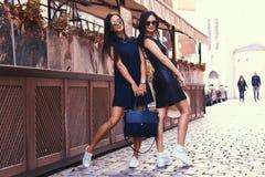 La brune deux sexy portant le noir élégant s'habille dans des lunettes de soleil, posant près d'un café de terrasse dans une vill Image libre de droits