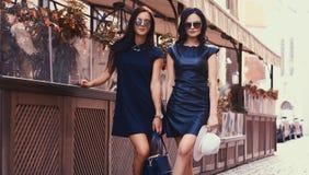 La brune deux sexy portant le noir élégant s'habille dans des lunettes de soleil, posant près d'un café de terrasse dans une vill Photos stock