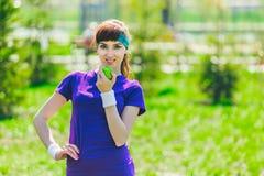 La brune entre pour des sports dehors, elle se tient sur l'herbe et tient une pomme verte et regarde l'appareil-photo Photos stock