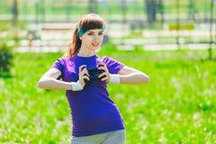 La brune entre pour des sports dehors, elle tient et tient une haltère dans des ses mains et regarde dans l'appareil-photo Photographie stock libre de droits