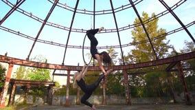 La brune et la blonde exécutent un cascade acrobatique complexe dans l'anneau, acrobaties aériennes, mouvement lent banque de vidéos