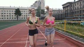 La brune et la femme châtain dans des vêtements de sprotivnaya font sproty sur la rue Style de vie sain banque de vidéos